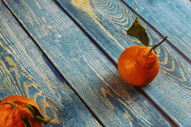 木製のテーブルの上の葉を持つ2つのみかん