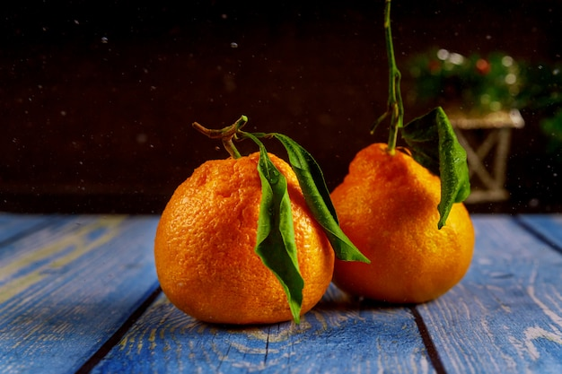 Two tangerines with leaf on wooden table