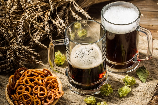 Two tankard beer with wheat and hops , basket of pretzels