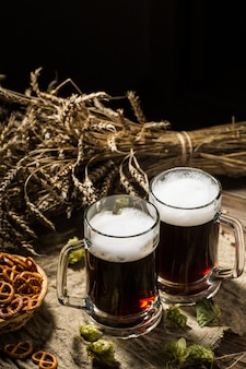 Two tankard beer with wheat and hops, basket of pretzels