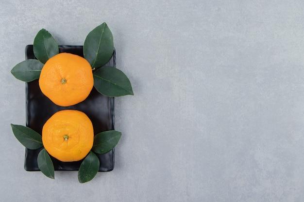 검은 접시에 두 개의 맛있는 클레멘타인 과일