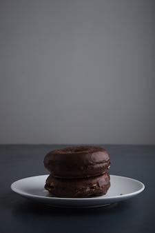 素朴な古い青い木製のテーブルに分離された白いセラミックの小さなプレートにチョコレートで艶をかけた2つのおいしい焼きたてのドーナツ。側面図