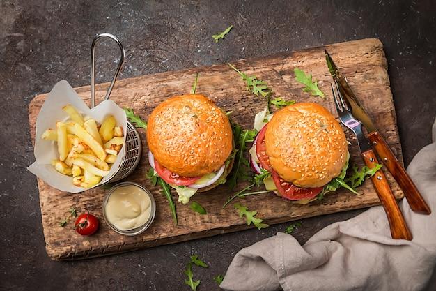 Два вкусных классических гамбургера из говядины на гриле с картофелем фри на деревенском черном столе с копией пространства