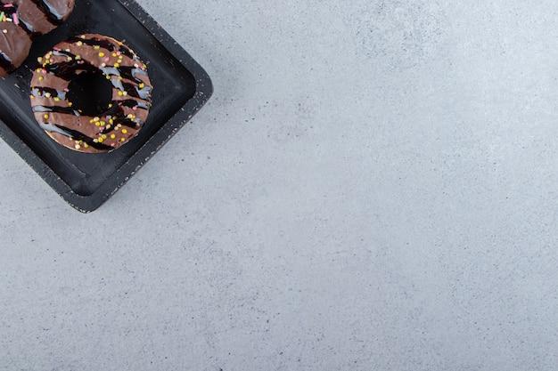 黒のまな板にふりかけたおいしいミニチョコレートケーキ2個。高品質の写真