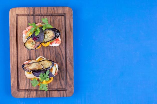 나무 판자에 튀긴 야채를 곁들인 두 개의 맛있는 토스트
