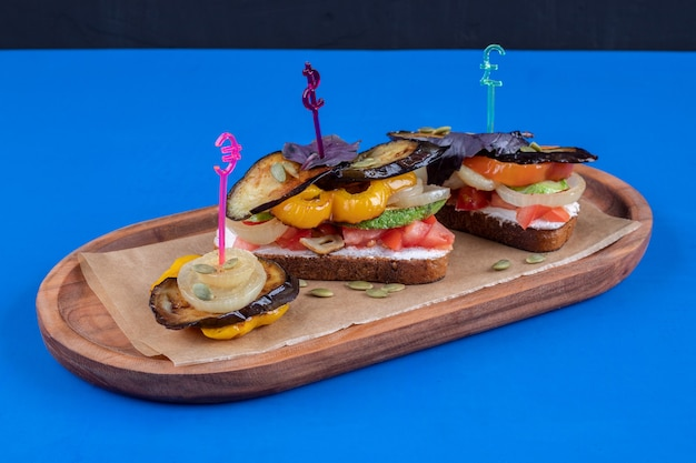 Two tasty toast with fried vegetables on wooden plate