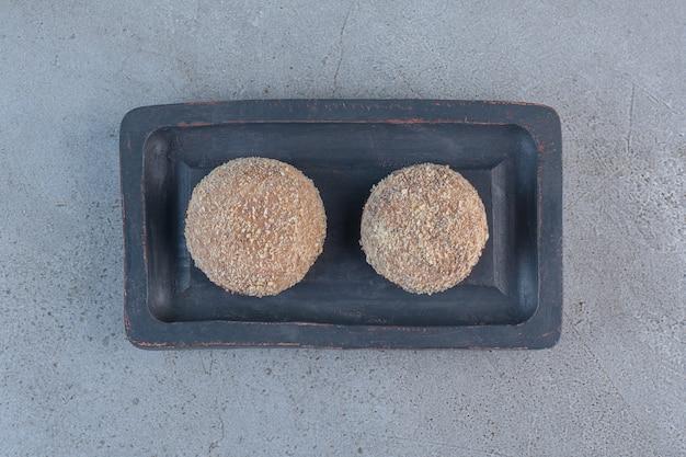 검은 접시에 두 개의 맛있는 트러플 볼이 놓여 있습니다.