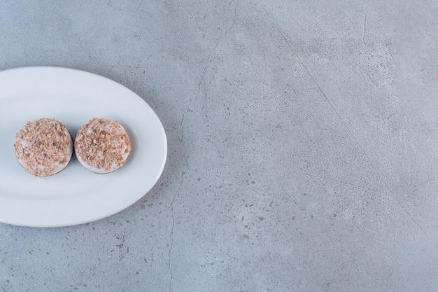 하얀 접시에 두 개의 맛있는 트러플 볼이 놓여 있습니다.