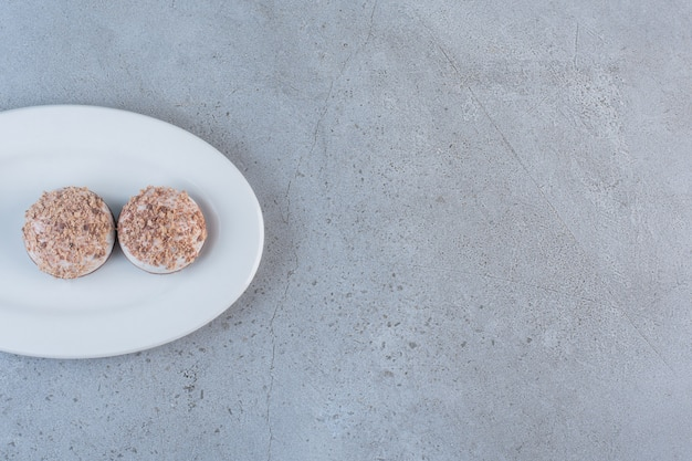 Two tasty truffle balls placed on white plate.