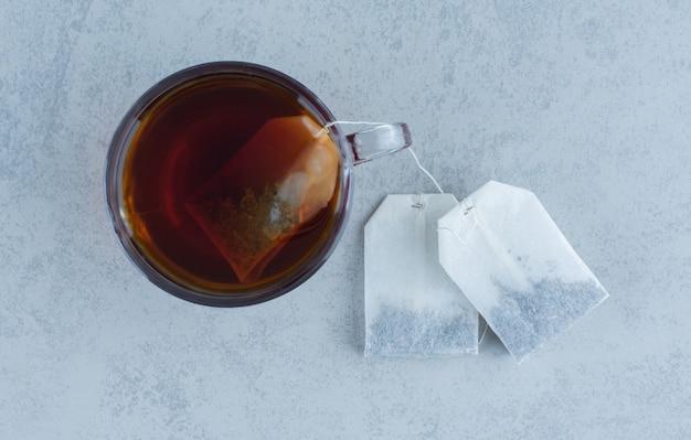 Due bustine di tè accanto a un bicchiere di tè su marmo.