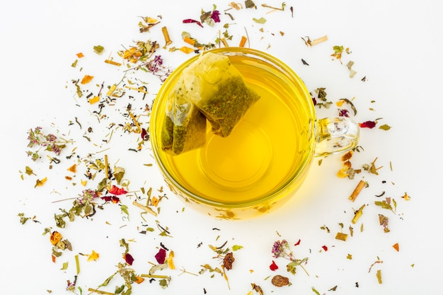 Two tea bags of green tea in glass mug with heap of dry tea leaves on a white background. organic herbal, floral, green asian tea for the tea ceremony. herbal medicine concept