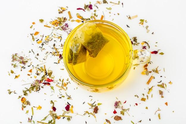 白い背景に乾燥茶のヒープとガラスのマグカップで緑茶の2つのティーバッグを残します。茶道のためのオーガニックハーブ、フローラル、グリーンアジア茶。漢方薬のコンセプト