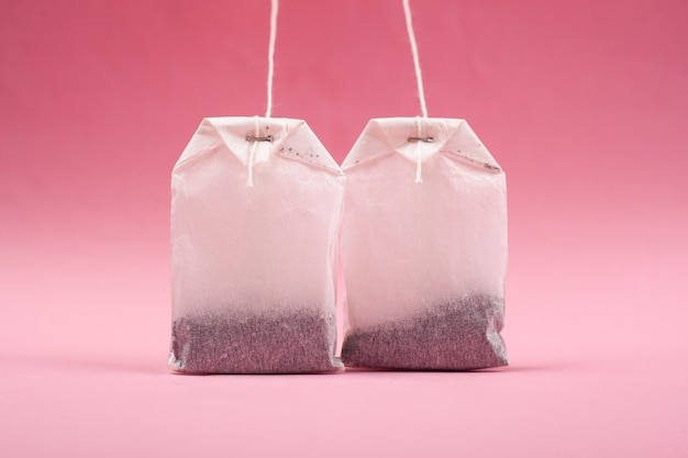 Two tea bags on a pink background.