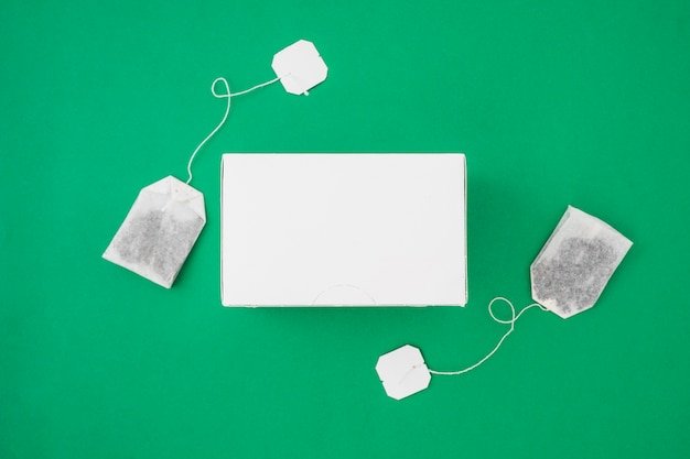 Two tea bags on the side of white box over the green background