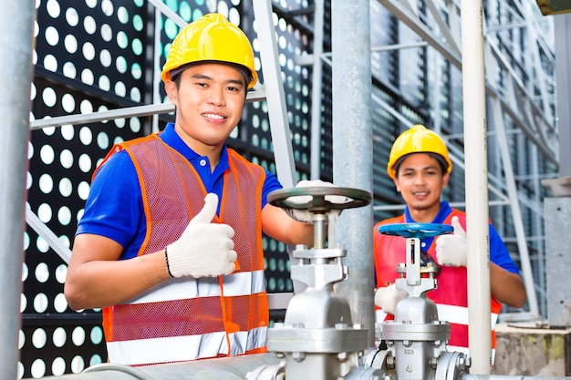 Two technicians or engineers working on a valve on building technical equipment or industrial site