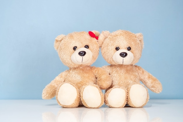 Two teddy bear sitting on a white table and blue background
