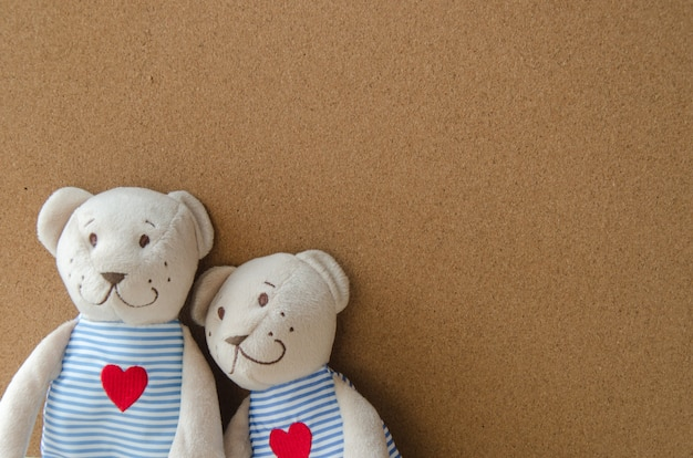Two teddy bear with heart on cork board background