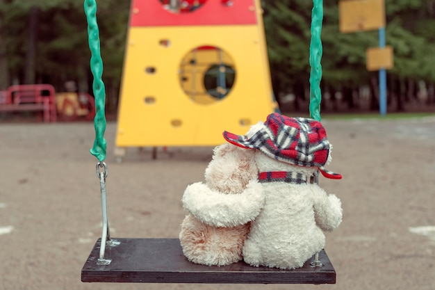 Two teddy bears hugging each other sitting on a swing. the concept of love, relationships.