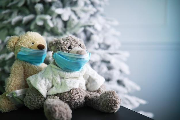 보호 마스크를 쓰고 있는 두 개의 테디베어. 코로나 바이러스 보호. 바이러스 확산을 방지하기 위해 마스크에 장난감 곰. 공간을 복사합니다.