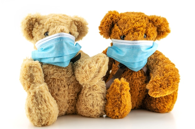 保護マスクを着用した2つのテディベア、白い背景の青い医療マスクに座っているテディベア、呼吸器疾患からの保護の概念、コロナウイルスの停止と大気汚染の概念。