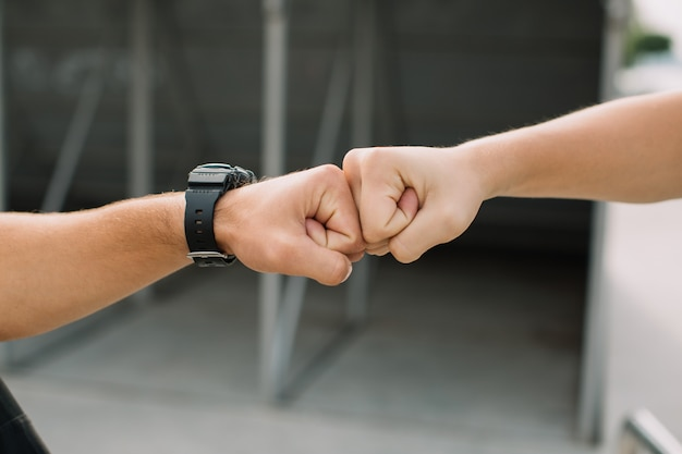 Two teen boys giving fist bump at meeting each other.