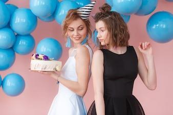Two teen cute fashion little girls holding happy birthday white cream cake.