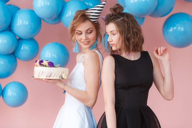 Two teen cute fashion little girls holding happy birthday white cream cake.