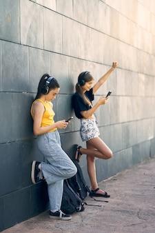 学校でテクノロジーを楽しんでいる2人の10代の少女