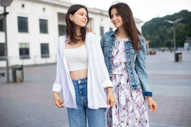 Two teen girls in casual clothes walking down the street in summer