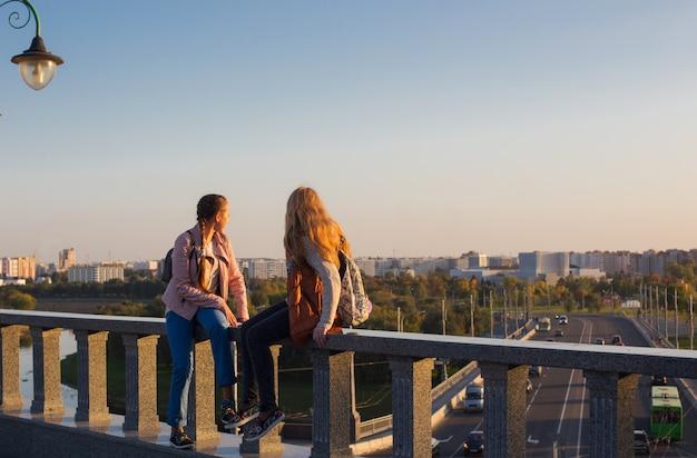 Две девочки-подростки на мосту в городе