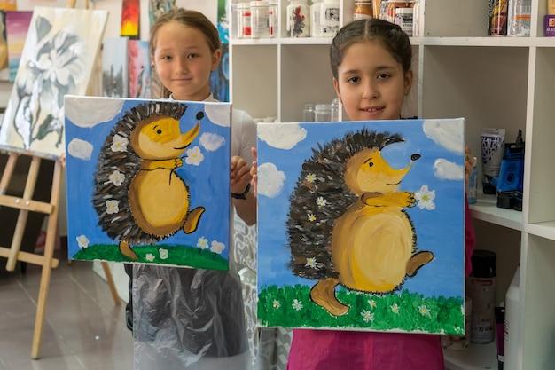 Две девочки-подростки хвастаются своими фотографиями. интерьер художественной школы для детей. концепция творчества и людей.
