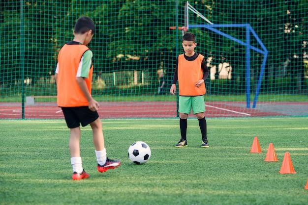 두 십대 선수가 축구 경기장에서 서로 축구 공을 전달합니다.