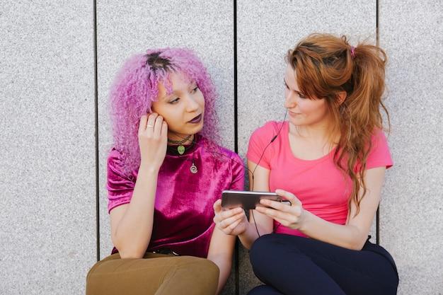 Два подростка женщина с красочной одеждой и разнообразием образа жизни, разделяя наушники и слушая музыку