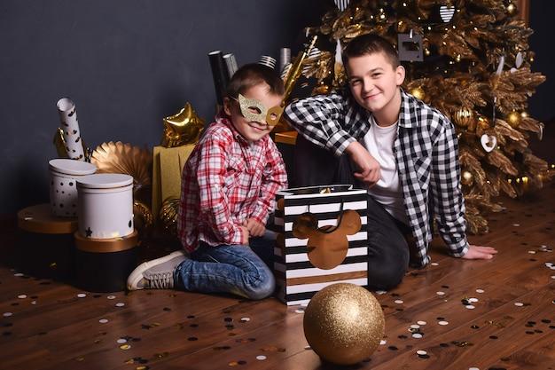 Два брата-подростка сидят на полу рождественской гостиной с подарками и улыбаются