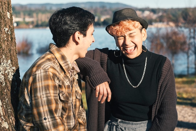 公園の木に座って、お互いを見ながら笑っている2人の10代の友人