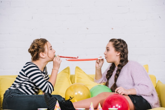 Two teenage girls blowing party horn sitting face to face on sofa with balloons