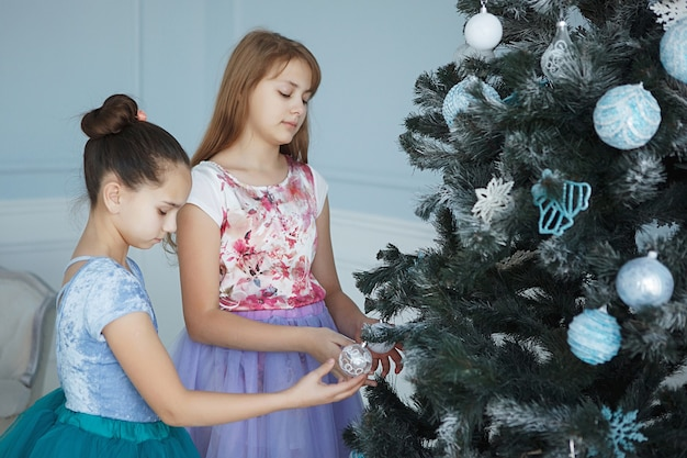 Two teenage girls decorate a christmas tree.