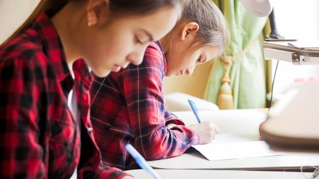 自己隔離で自宅で学校の宿題をしている2人の10代の少女。
