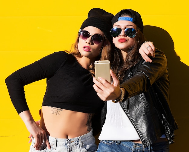 Two teenage girls friends in hipster outfit outdoors make selfie on a phone.