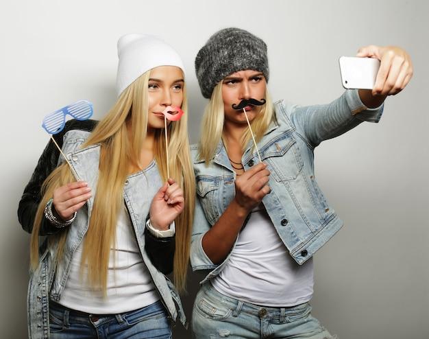 Две подруги-девочки-подростки в хипстерской одежде делают селфи по телефону.