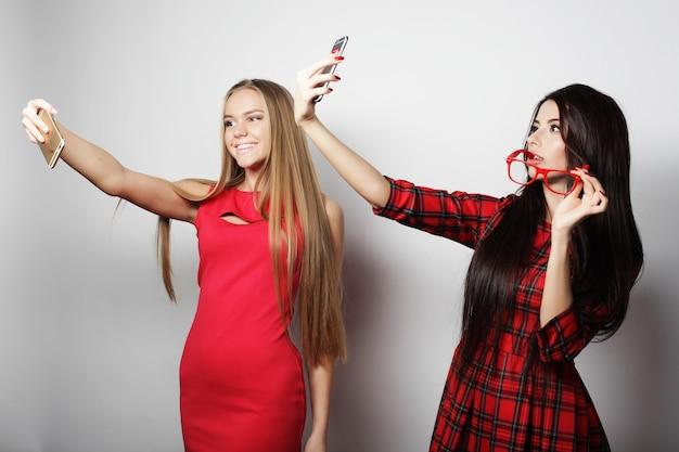 힙스터 복장을 한 두 명의 십대 여자 친구가 전화로 셀카를 만듭니다.