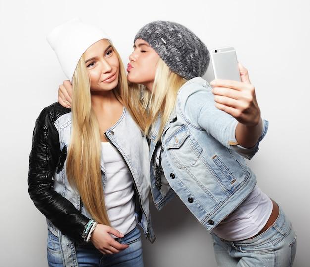 流行に敏感な衣装を着た2人の10代のガールフレンドが電話で自分撮りをします。
