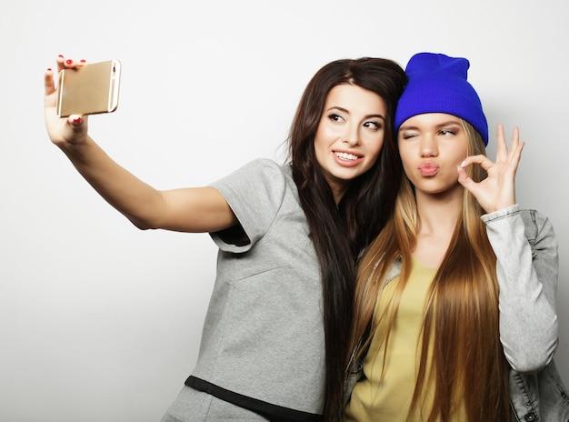 힙스터 복장을 한 두 명의 십대 여자 친구가 흰색 배경 위에 셀카를 만듭니다.