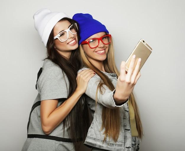 流行に敏感な服装の2人の10代の女の子の友人が白の上に自分撮りをします