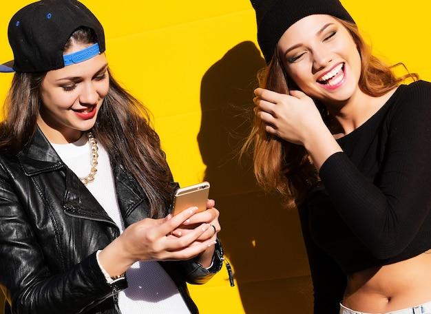 屋外で流行に敏感な衣装を着た2人の10代のガールフレンドが電話で自分撮りをする