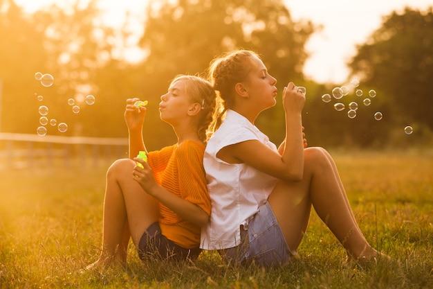 2人の10代の少女が公園で楽しんでいます。屋外の2人の友人。泡をしている夏の人々