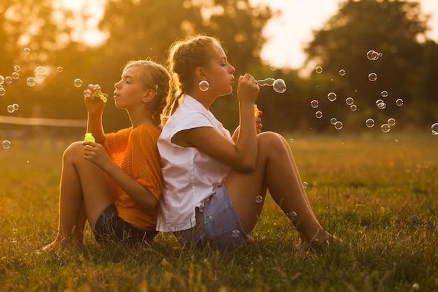 두 명의 십대 소녀가 공원에서 즐거운 시간을 보내고 있습니다. 두 친구 야외입니다. 거품을하는 여름 사람들