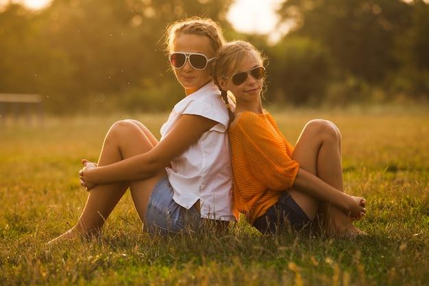 두 명의 십대 소녀가 공원에서 즐거운 시간을 보내고 있습니다. 두 친구 야외입니다. 안경에 여름 사람들