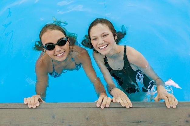Two teenage girls having fun in the swimming pool.