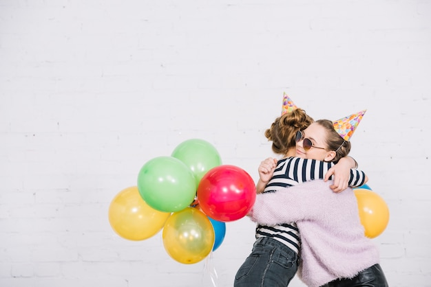 Two teenage girls holding balloons in hand embracing each other against white backdrop